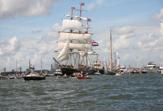 Boten met de Nederlandse en Amsterdamse vlaggen varen door het kanaal