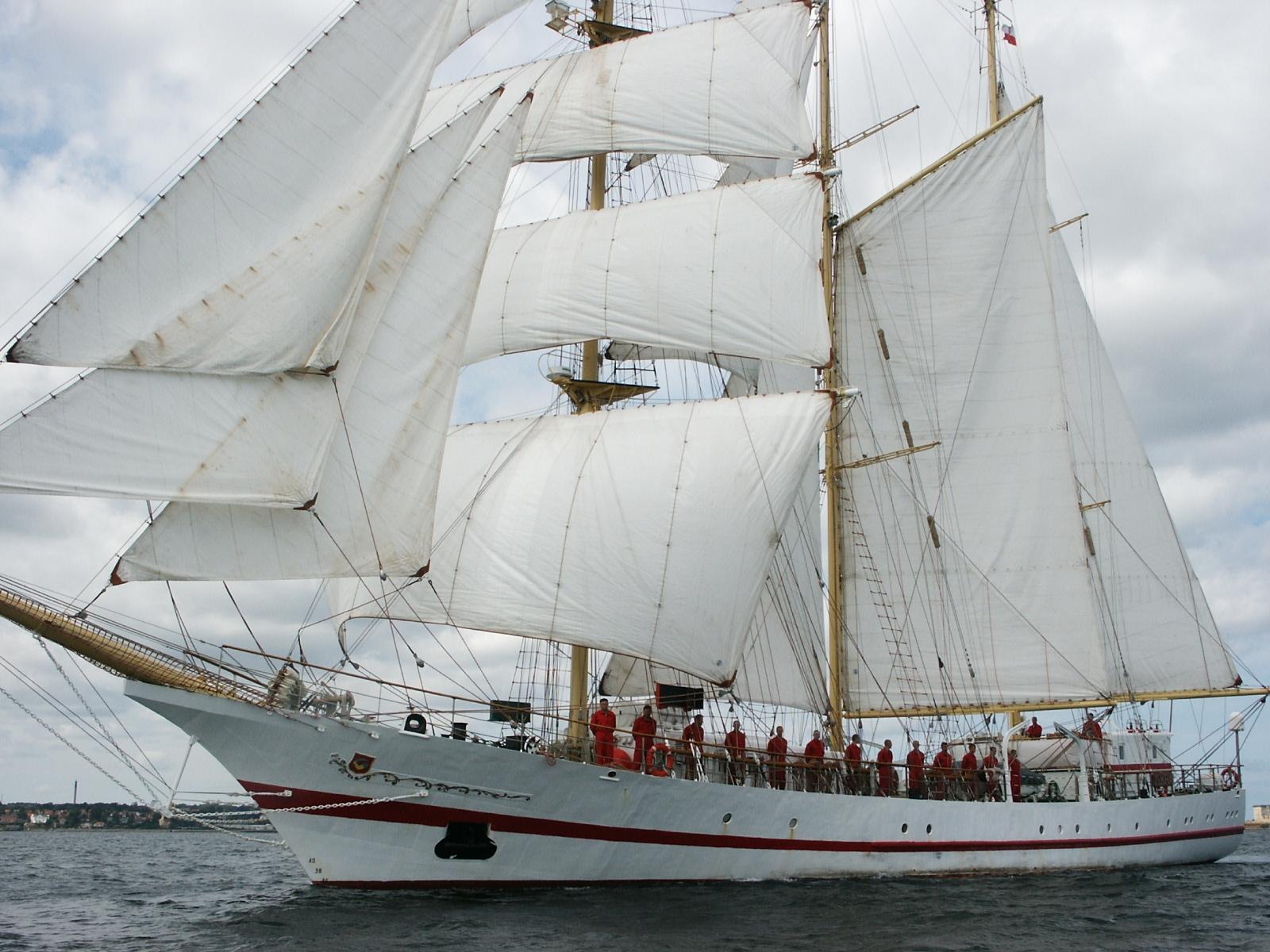 Bemanning van Tall Ship de Iskra staan in hun rode kleding aan de zijkant van het schip