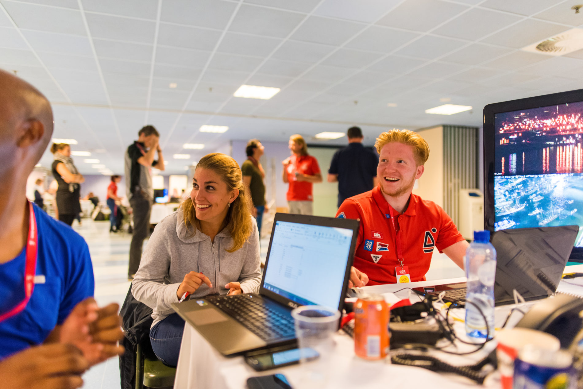 twee lachende medewerkers van SAIL aan een bureau