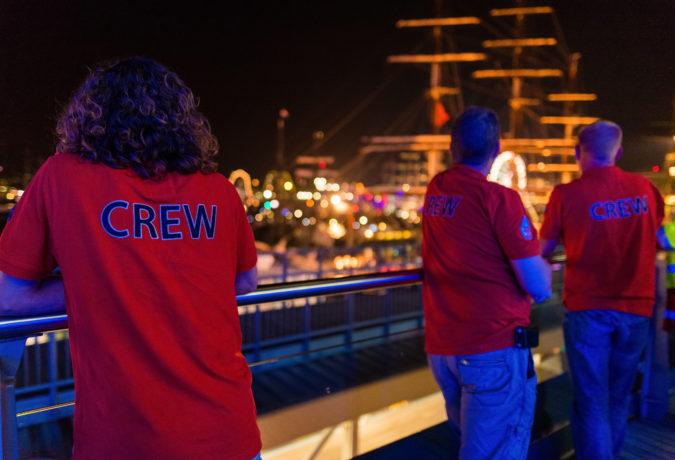 Drie medewerkers met een rood t-shirt waar Crew achterop staat