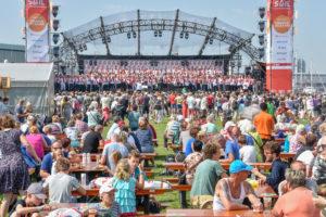 Groot podium op een festival terrein gevuld met mensen