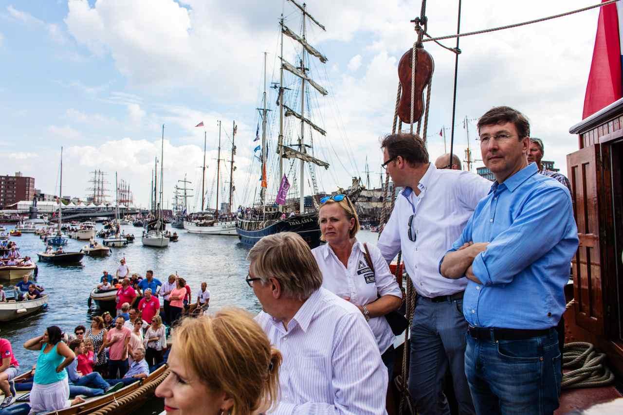 Mensen op een schip die kijken naar de varende boten op het Ij-kanaal