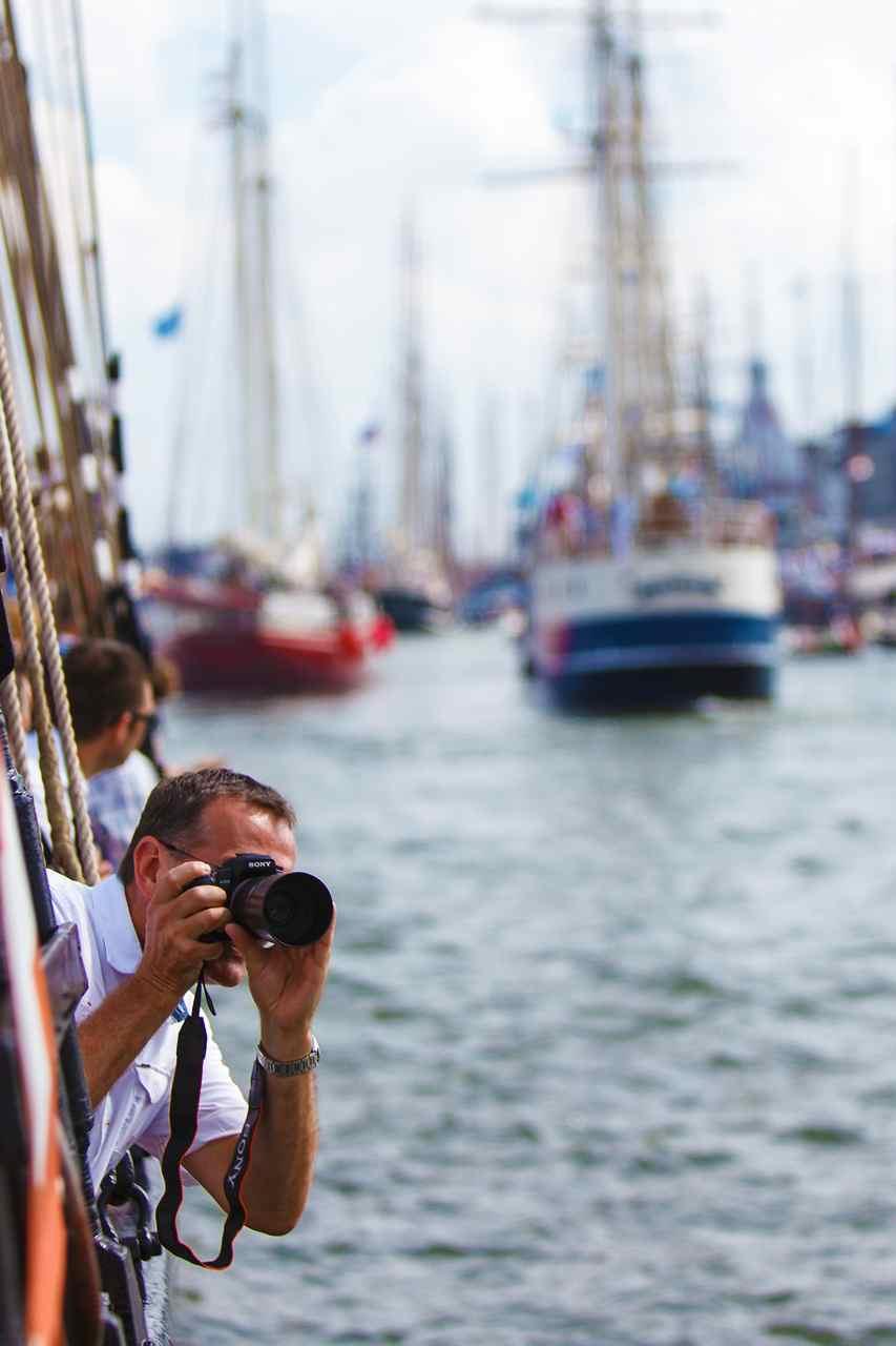 Fotograaf die uit de boot hangt om een foto te schieten