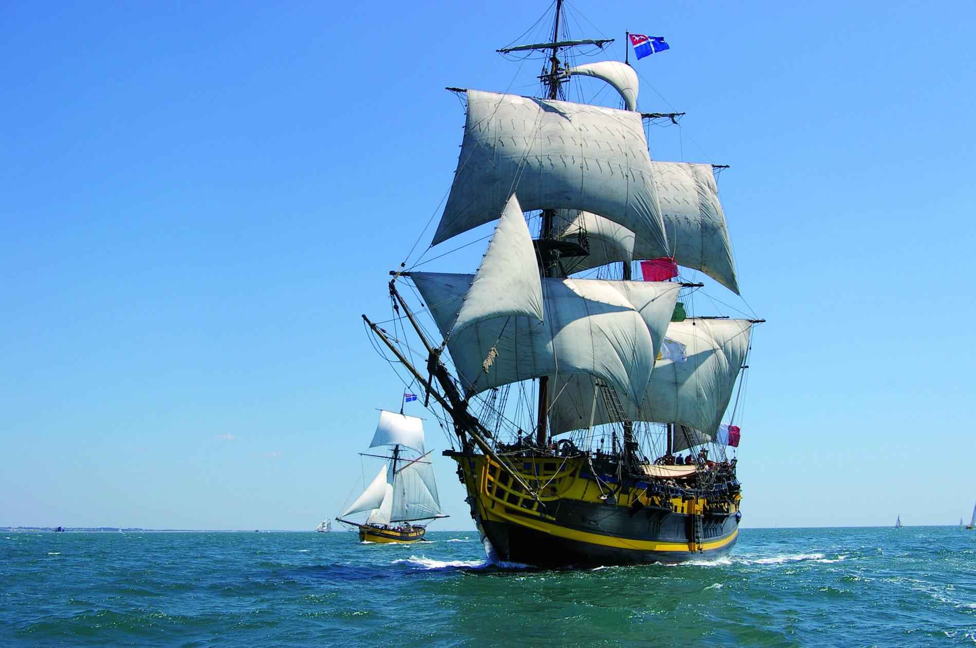 Etoile Du Roy met de gele bekende details vaart door het water vergezeld door dochterboot