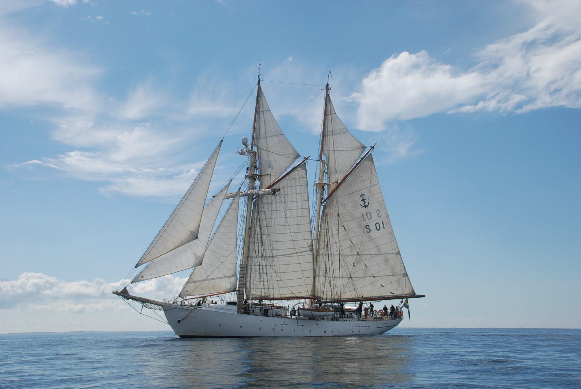 Tall Ship Gladan ligt in een stille zee met wolken op de achtergrond