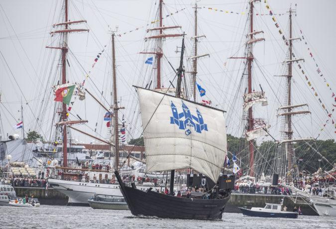 Houten donkere zeilboot met witte mast en blauw logo