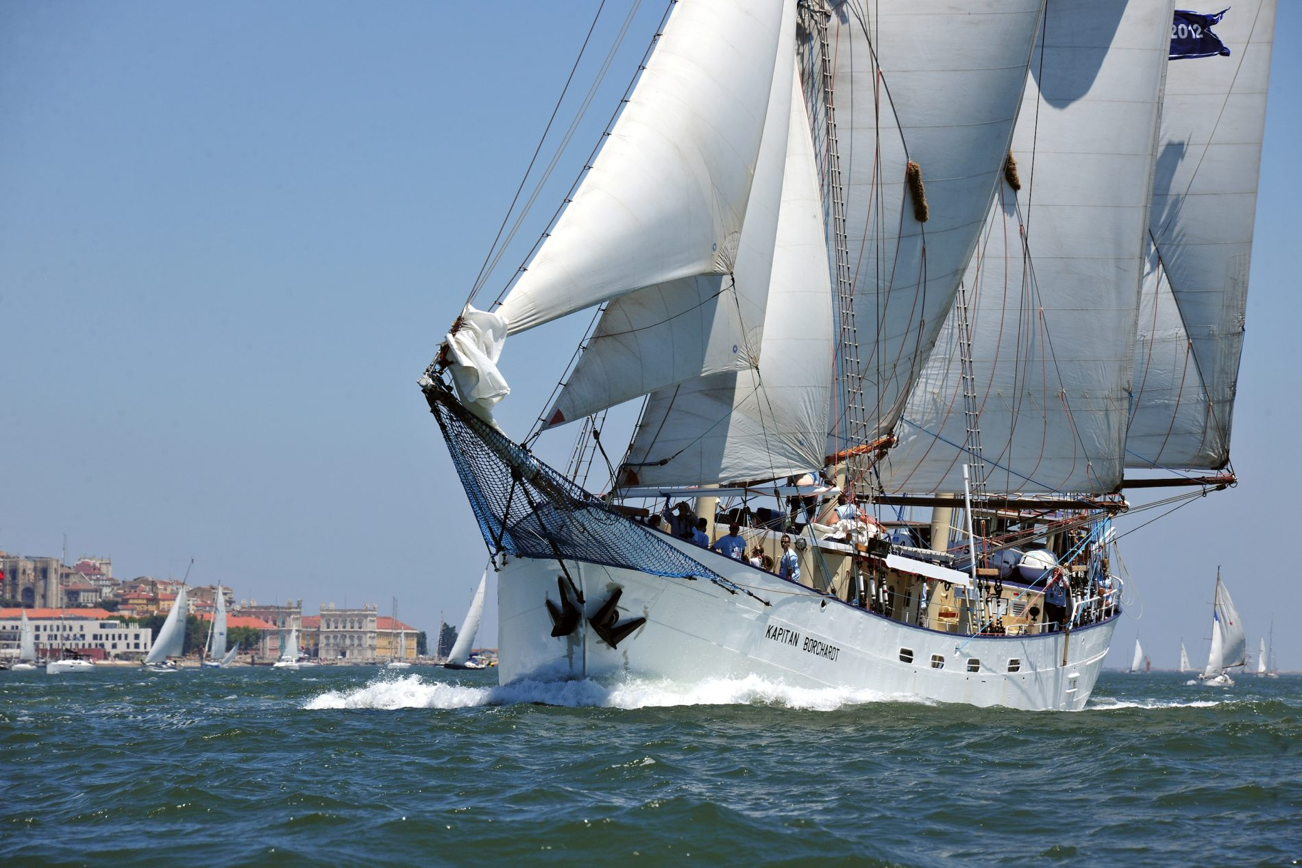 Kapitan Borchardt en zijn bemanning varen voor de kust van een dorp