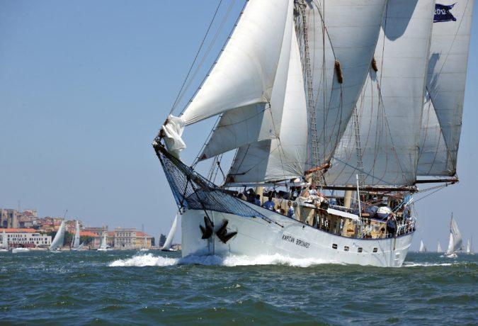 Schip Kapitan Borchardt en zijn bemanning varen voor de kust van een dorp