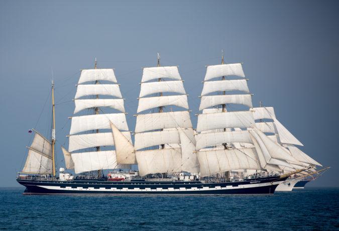 Tall Ship Kruzenshtern in de zee met alle zeilen uit en twee andere boten op de achtergrond