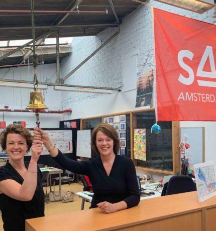 Twee mensen die aan de bel trekken in het kantoor van SAIL Amsterdam