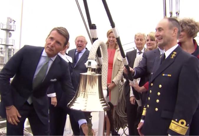 De directie van SAIL en hun gasten luiden een bel aan boord van een schip
