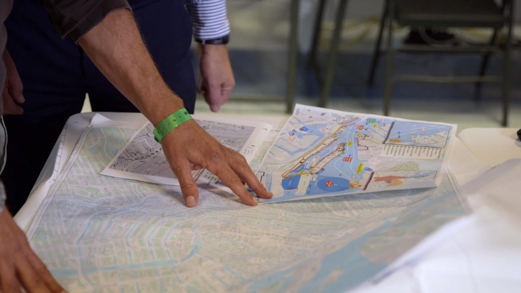 Twee handen die een kaart van de stad Amsterdam op een tafel vasthouden