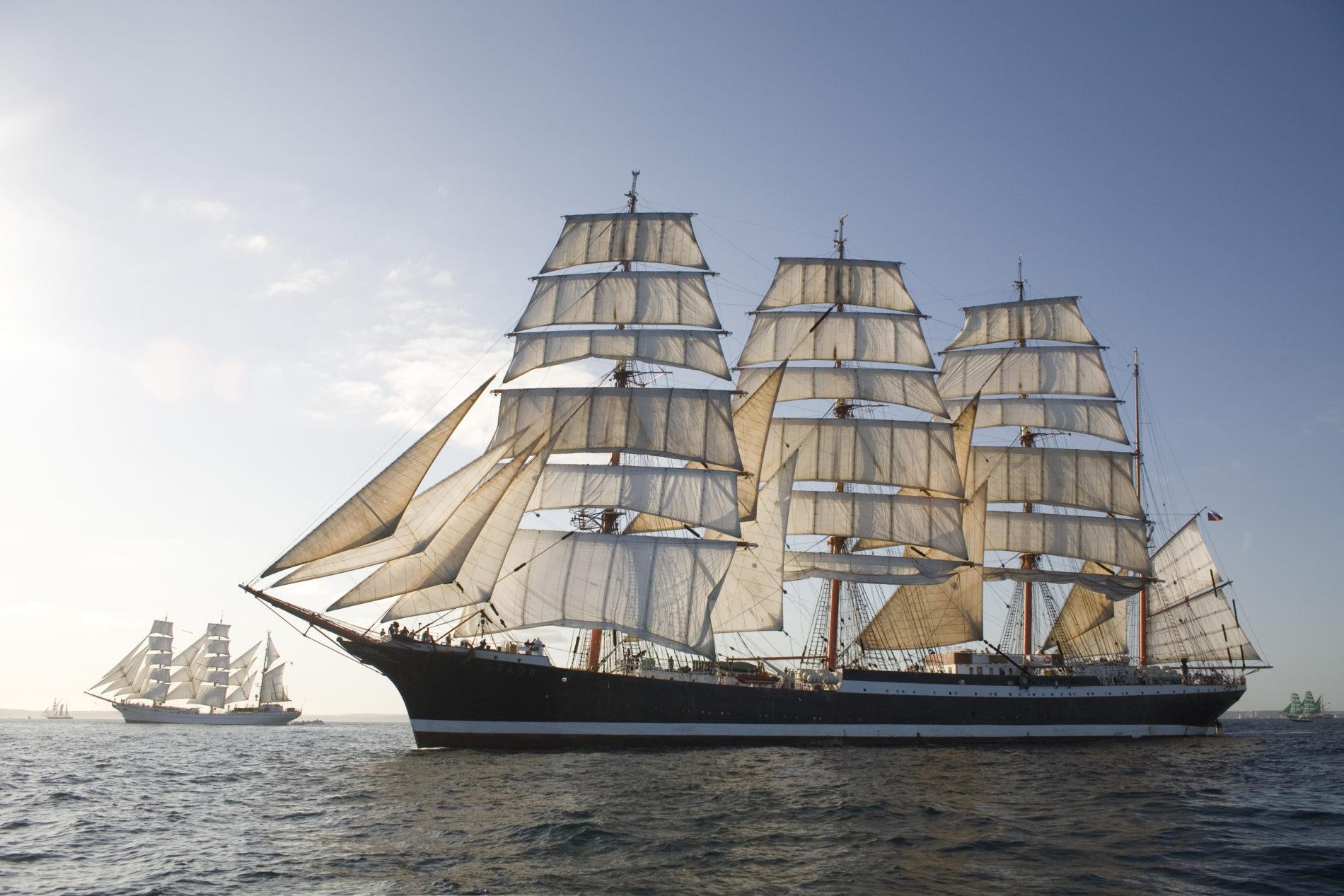 De bark Sedov ligt rustig in het water met schepen op de achtergrond