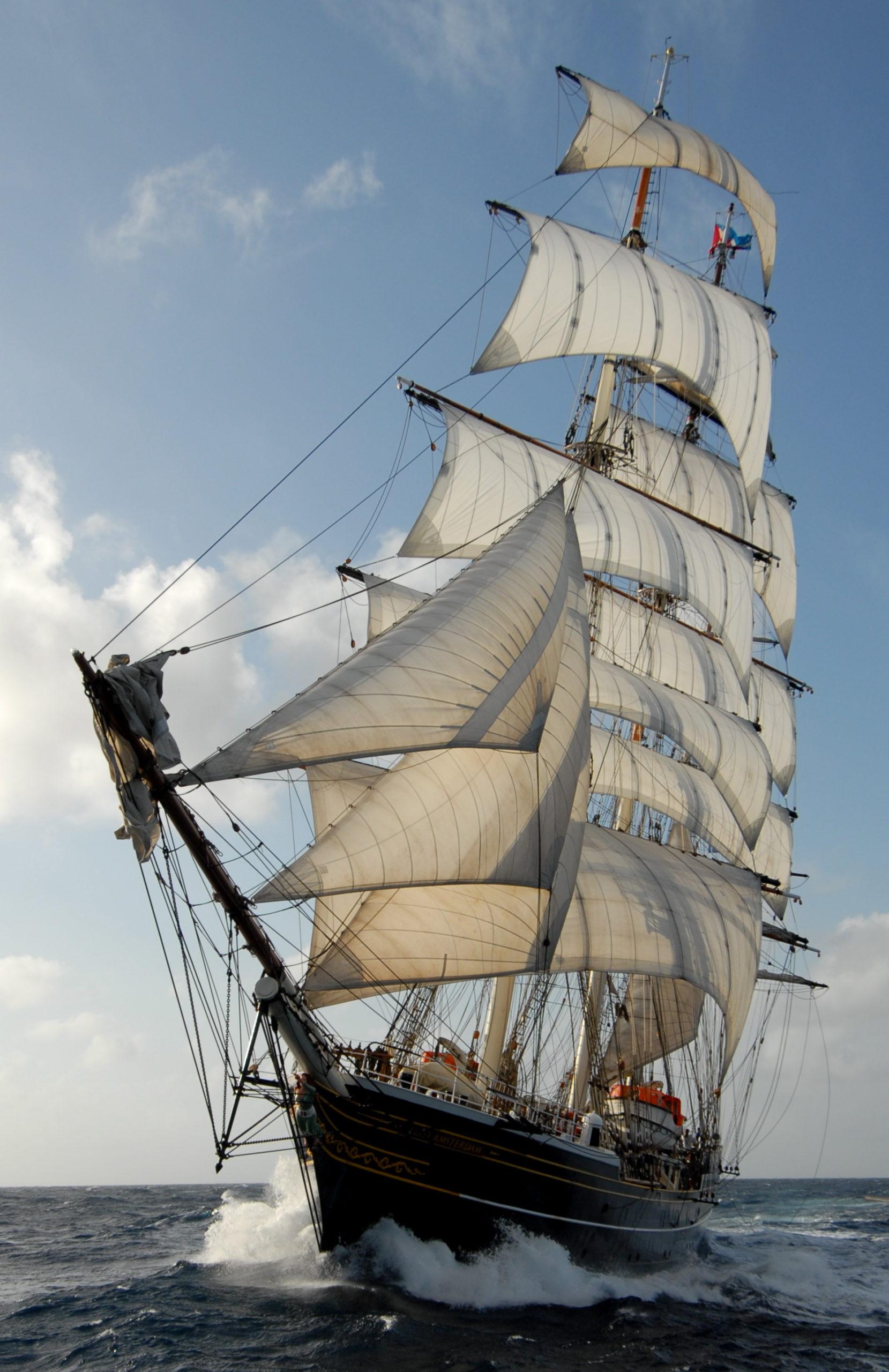 De clipper Stad Amsterdam vaart door de zee terwijl de golven tegen de boot slaan