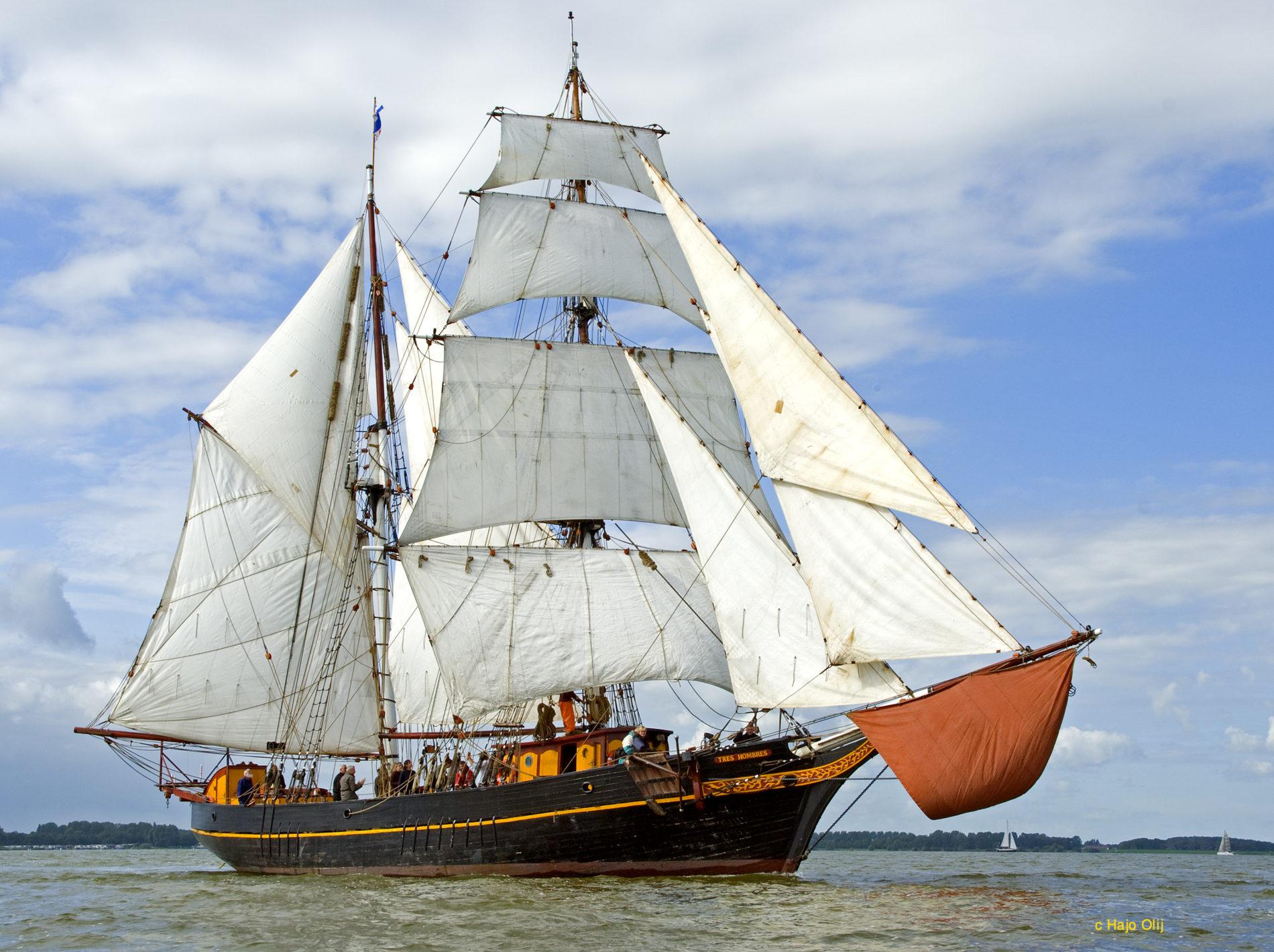 Zeilend vrachtschip Tres Hombres in het water met zijn bekende gele streep