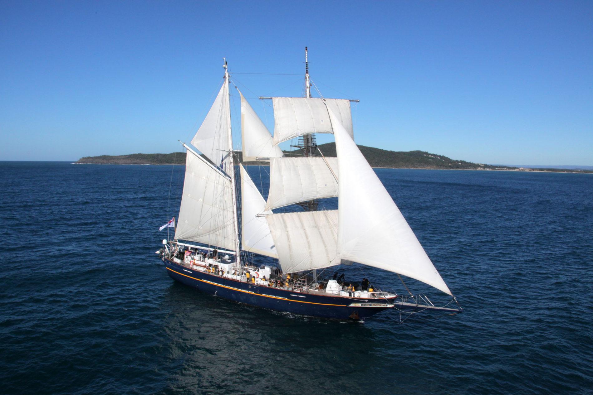 Stille zee met een eiland op de achtergrond en de Young Endeavour varend in de voorgrond