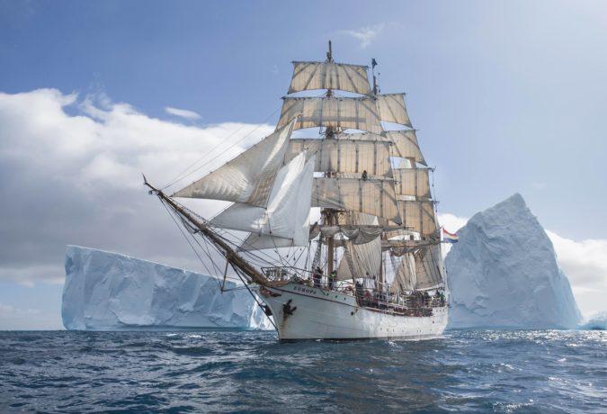 De bark Europa in de zee met ijsbergen op de achtergrond