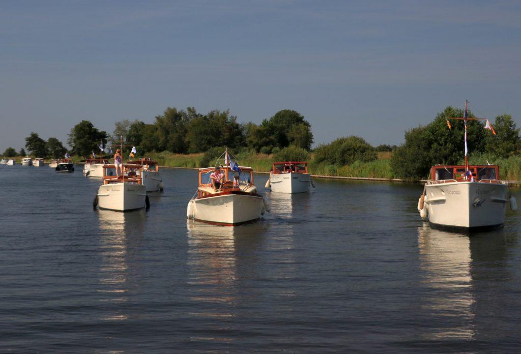 Allemaal dezelfde witte motorboten in het kanaal met gras op de oever - Vereniging Oude Glorie