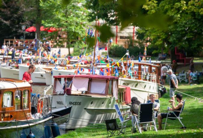 Drie mensen zitten op een stoel in het gras met allemaal boten en vlaggen op de achtergrond - Vereniging Oude Glorie