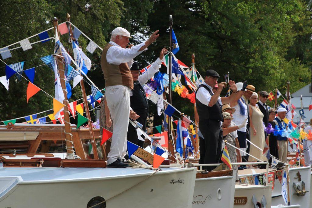 aangemeerde boten met zwaaiende mensen erop - Vereniging Oude Glorie