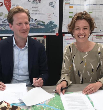 Twee mensen aan een tafel die een contract tekenen