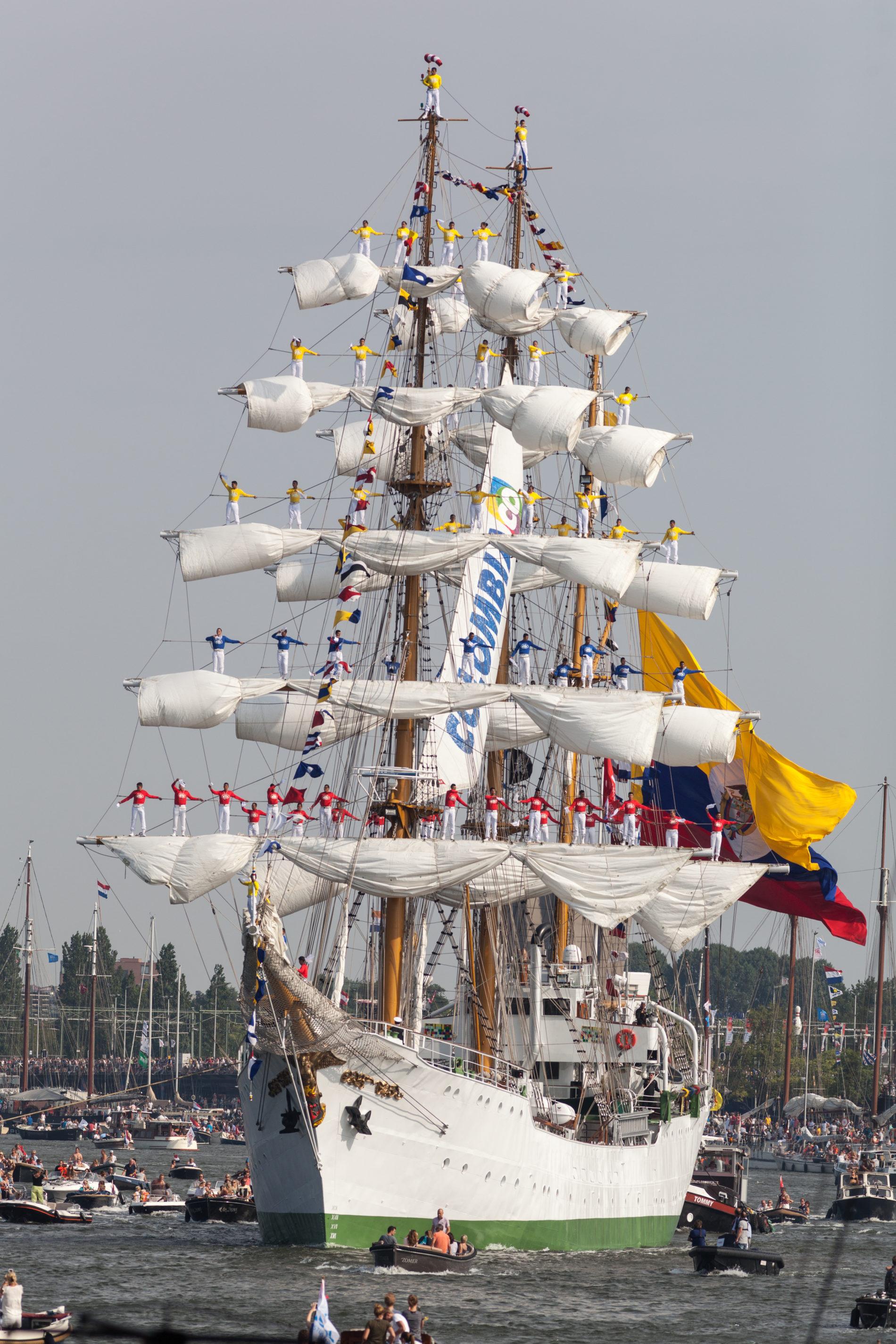 Bemanning van de ARC Gloria staan in de masten van het schip terwijl het de haven in vaart