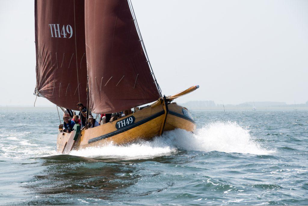 Stichting behoud hoogaars vaart met een van hun schepen door het water