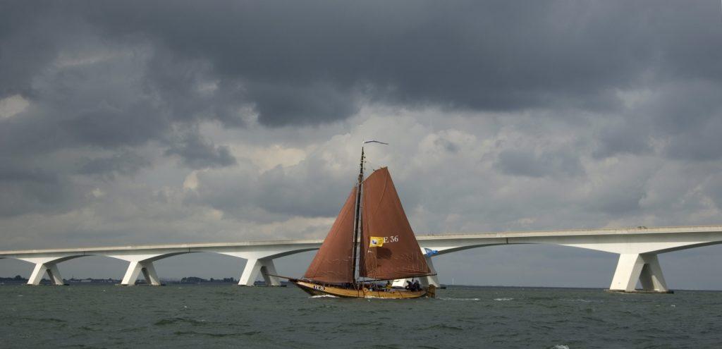 Een oude Hoogaars vaart voor een lange brug