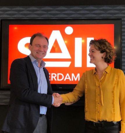 Mensen schudden elkaar de hand voor een scherm met het SAIL logo