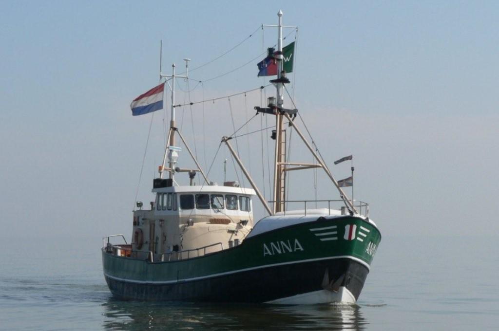 Groene boot Anna met Nederlandse vlag - stichting kotterzeilen en kotterbehoud