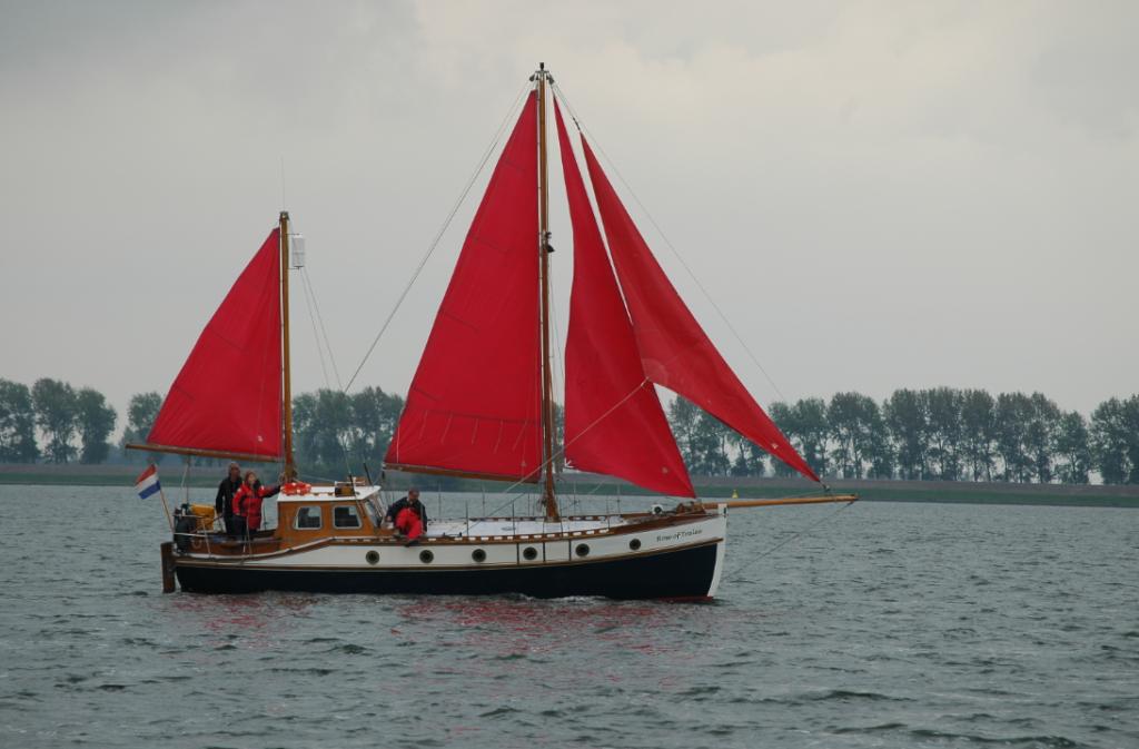 Zeilboot met rode zeilen op een rivier - Stichting Kotterzeilen en kotterbehoud