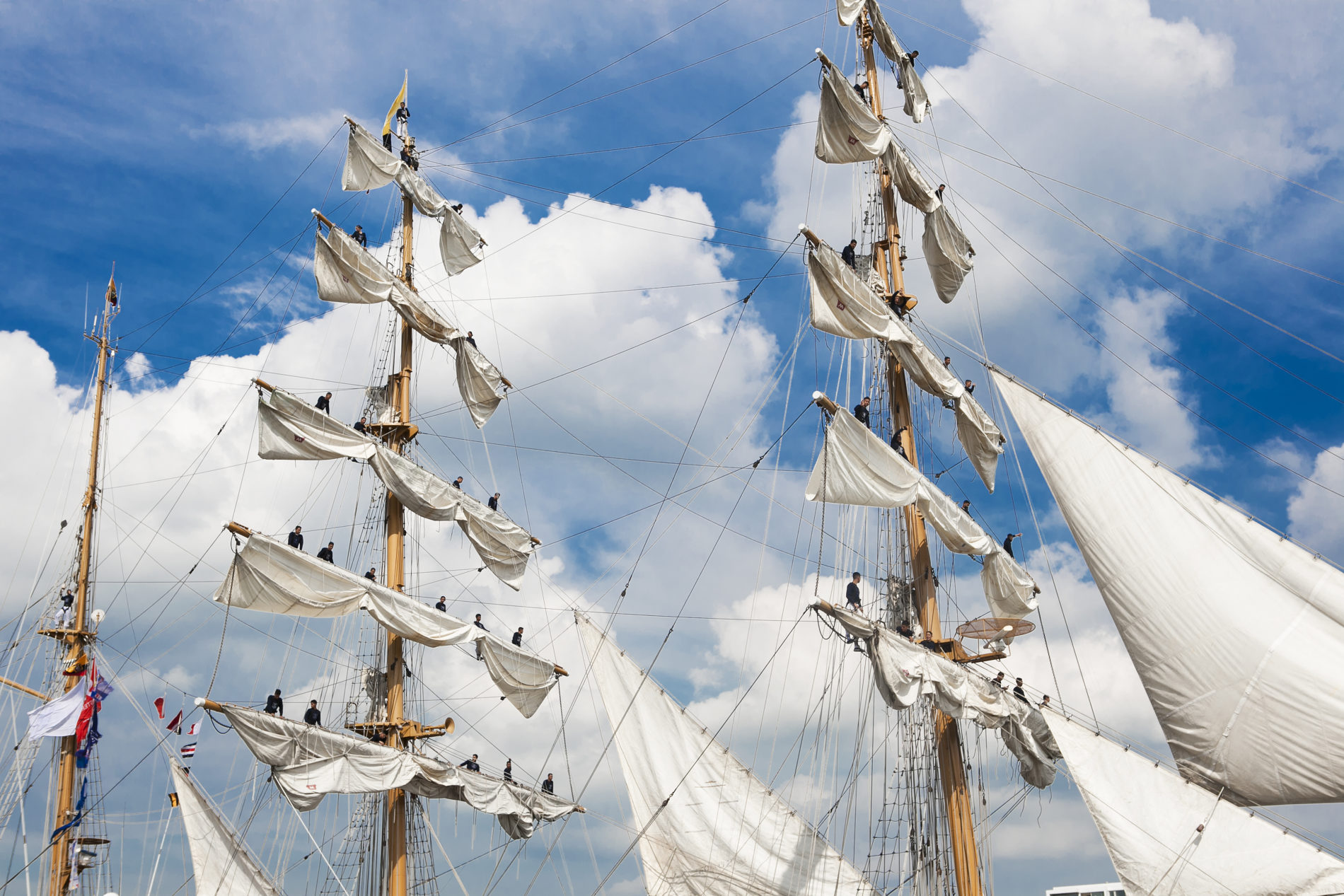 Bemanningsleden van de GUayas staan de de masten van het schip