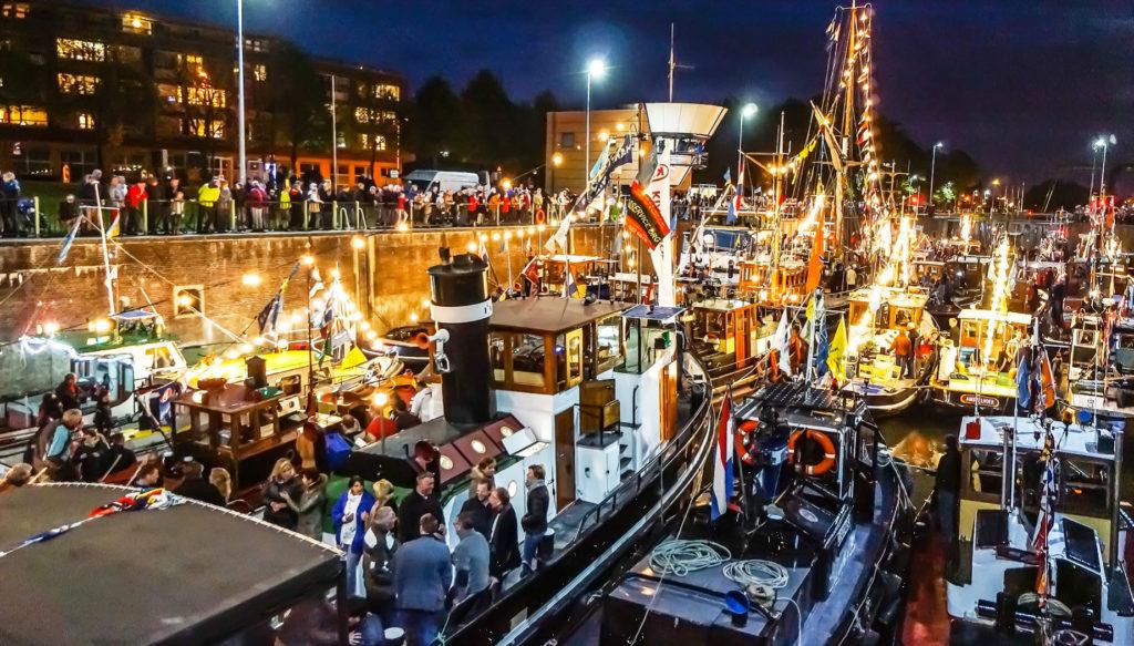Een groep boten naast elkaar met de lichten aan - Stichting de Motorsleepboot
