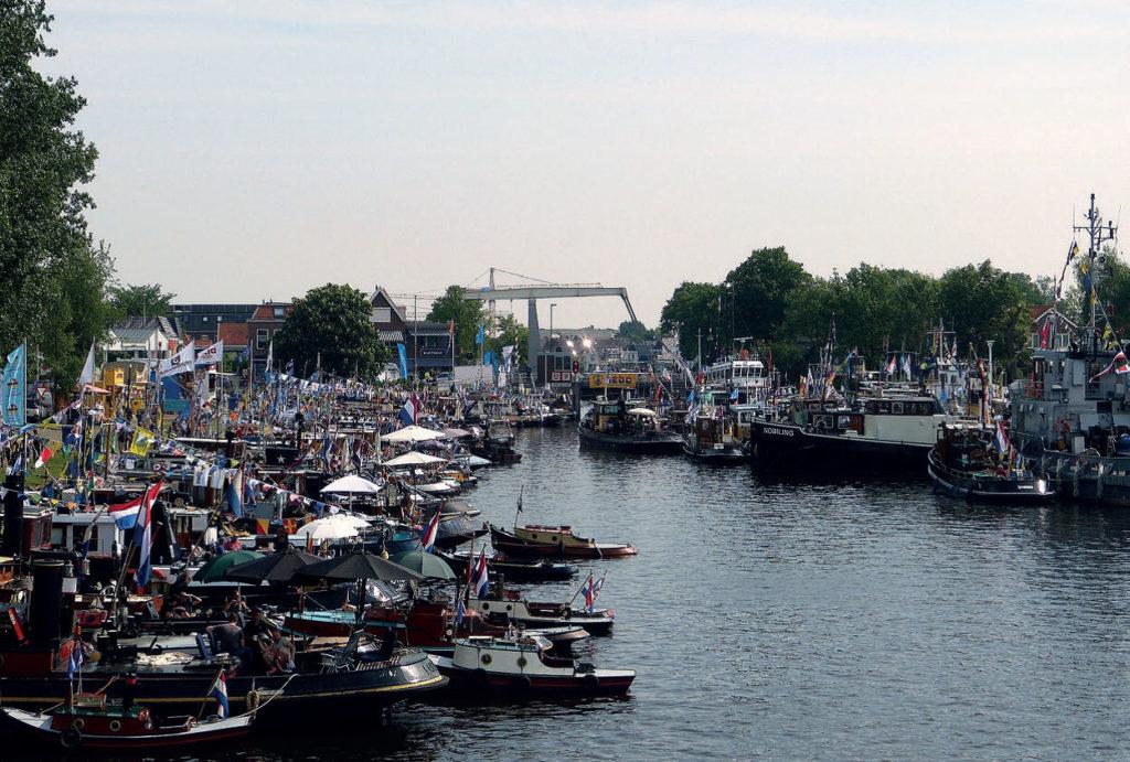 Vele boten en vlaggen in het kanaal - Stichting de Motorsleepboot