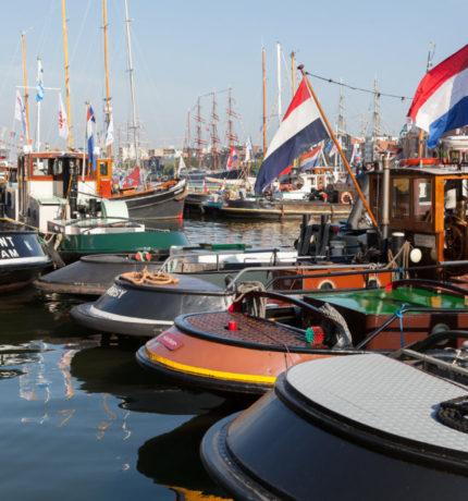 Schepen liggen stil in het water en tonen de Nederlandse vlag