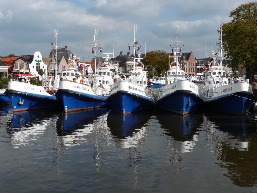 Vijf dezelfde schepen op een rij liggend in het water - ORG