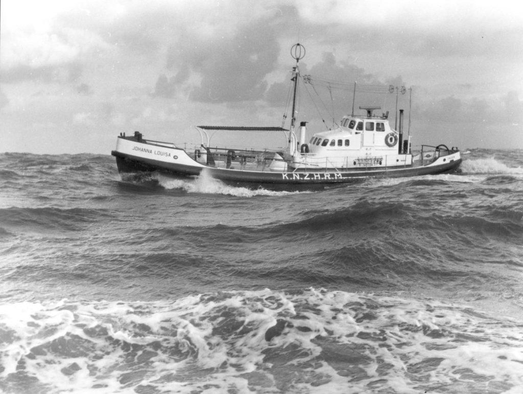 Zwart wit foto van een boot die door golven wordt belaagd