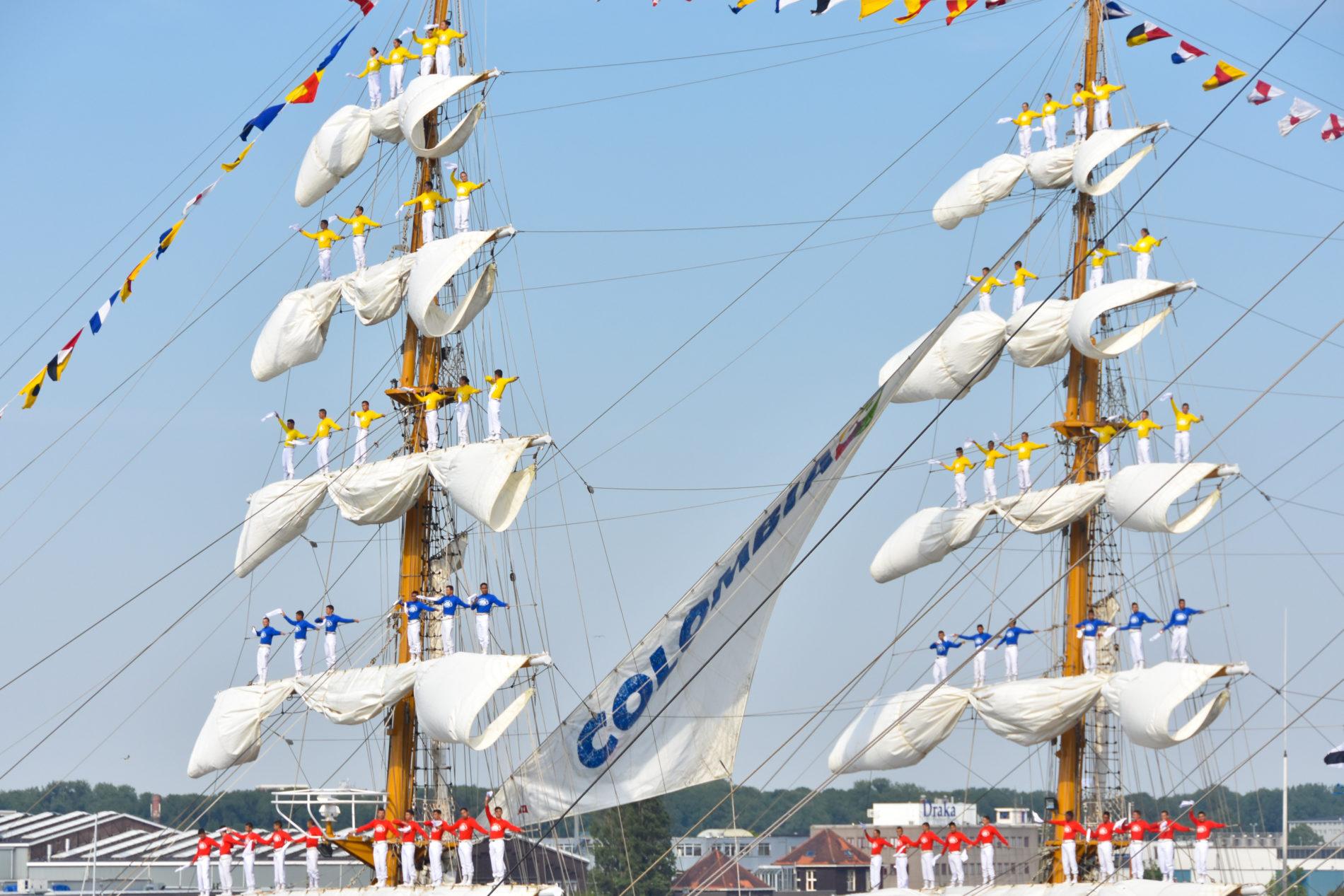 Bemanning van de ARC Gloria staan in de masten van het schip