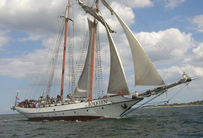 Het zeilschip Tolkien met mensen aanboort vaart op een meer