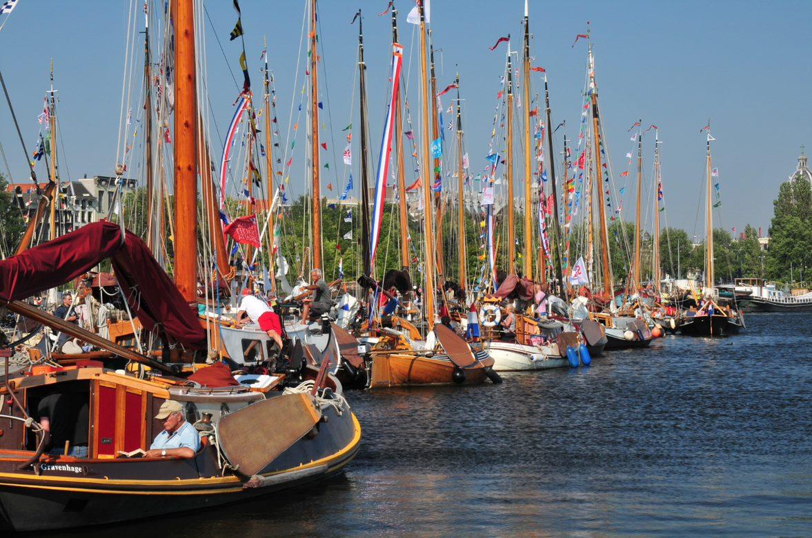 Vele diverse ouden boten met vlaggen in hun masten liggen aan de zijkant van het water