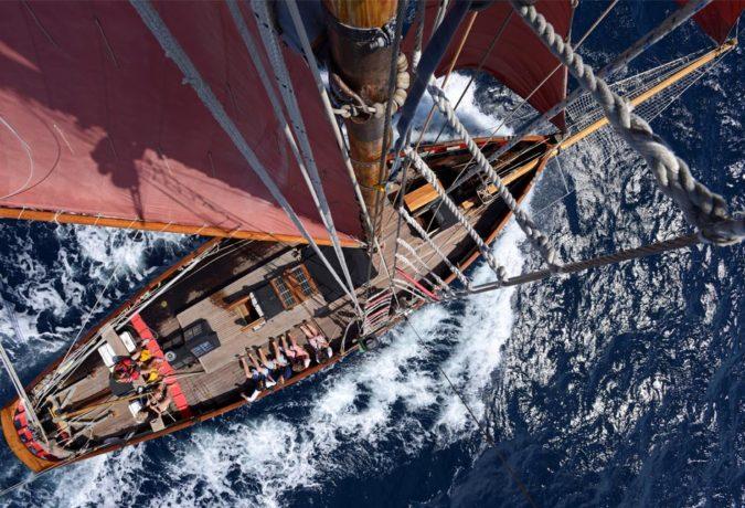 Tall Ship Jolie Brise klapt door de golven en heeft zijn rode zeilen uit